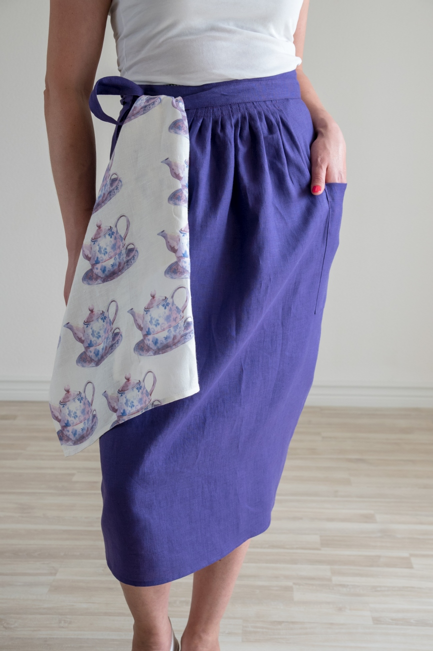 Purple washed linen half apron with adjustable width and a pocket